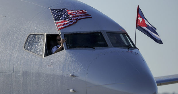 An American Airlines plane fluttering US and Cuba national flags is seen uppon arrival at Jose Marti International Airport becoming the first Miami-Havana commercial flight in 50 years, coinciding with the beginning of the tributes to late Cuban leader Fidel Castro, on November 28, 2016 in Havana.  / AFP PHOTO / YAMIL LAGE